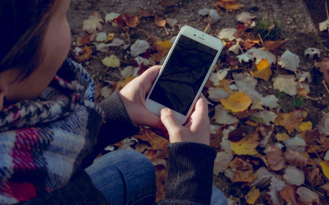 Hold deg okkupert med smarttelefonen mens barna leker